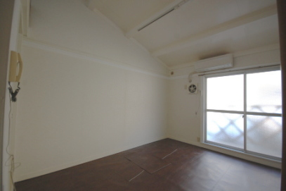 同じ部屋を白系統のクロスおよび濃い色のクッションフロアを貼った例
